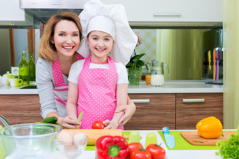 Happy young mother with daughter cooking. royalty free stock photography