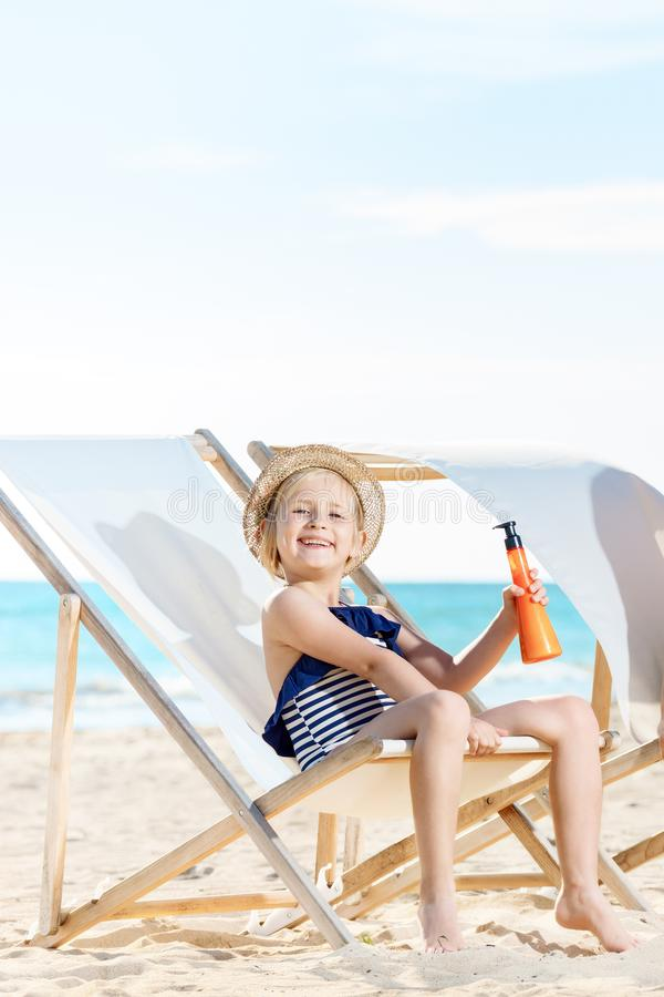 Girl sitting on beach chairs and holding sun scre stock image