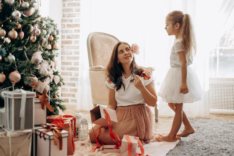 Happy young mother with flower in her hair and her little daughter in nice dress sit near the New Year`s tree and open stock images