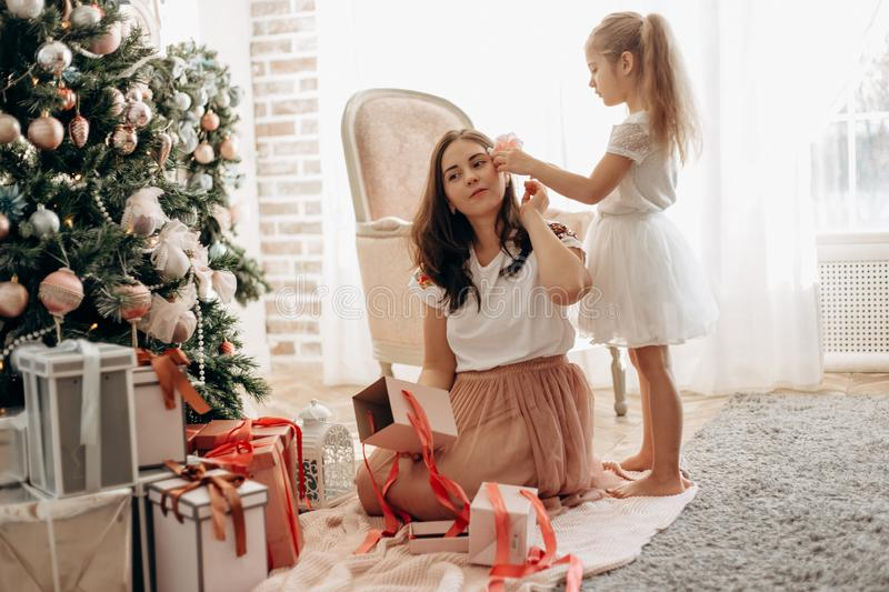Happy young mother and her  little daughter in nice dress sit ne royalty free stock images