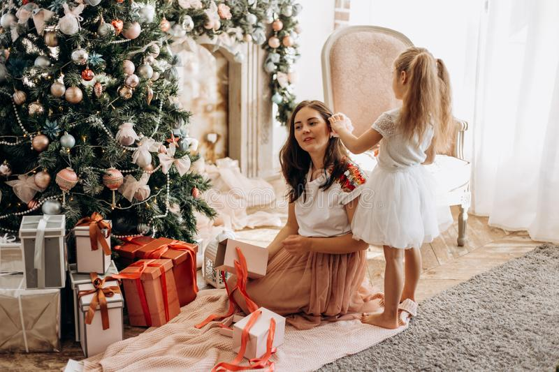 Happy young mother and her little daughter in nice dress sit near the New Year`s tree and open New Year`s gifts in the stock photography