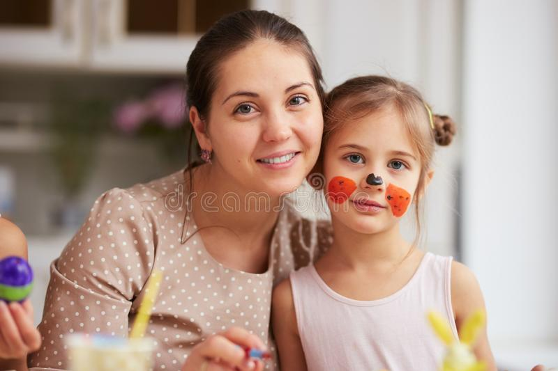 Happy young mother and her little daughter with painted face in the cozy light kitchen. stock image
