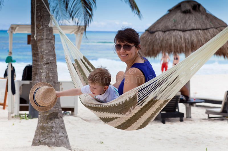 Happy young mother with her son in a hammock stock image