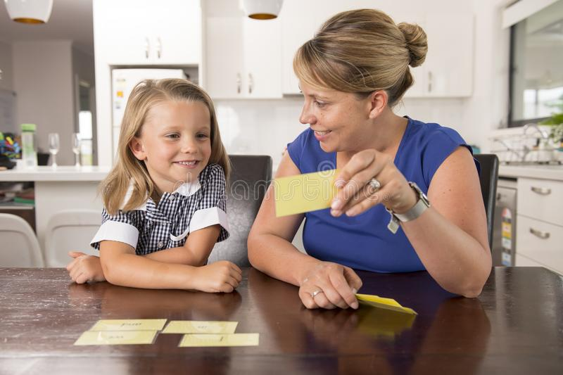 Happy young mother and her sweet and beautiful little daughter playing card game at home kitchen smiling and having fun together royalty free stock photo