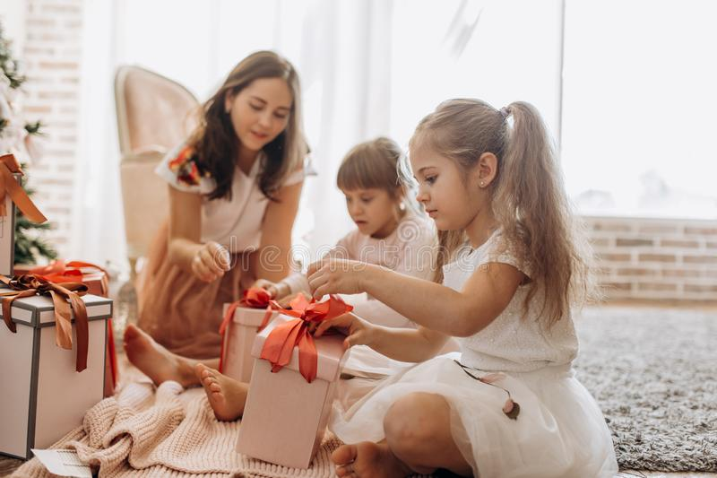 Happy young mother and her two charming daughters in nice dresses sit on the carpet and open New Year`s gifts in the stock photo