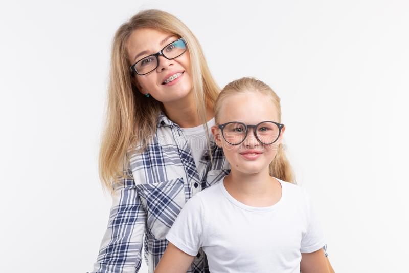 Happy young mother and laughing kid in fashion glasses have fun on white background royalty free stock photography