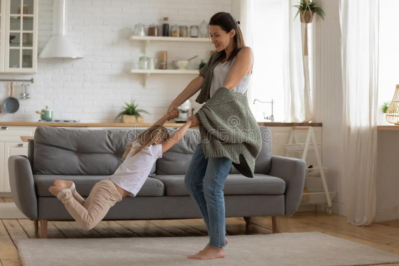 Happy mother lifting spinning child daughter dancing in modern kitchen royalty free stock photos