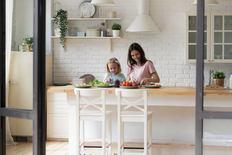 Smiling family of two cooking, communicating, enjoying weekend time. stock image