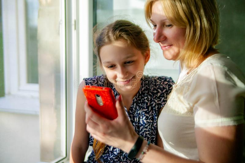 Beautiful Mom showing to her daughter something on her phone. royalty free stock photos