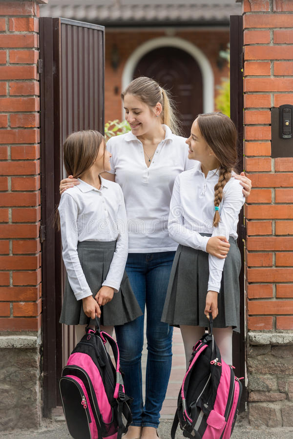 Happy young mother looking at her daughters leaving for school stock photo