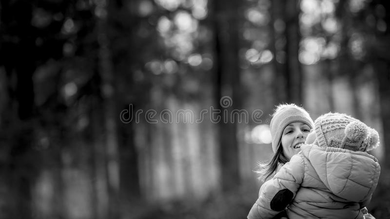 Happy young mother outside in nature holding her baby in her lap stock photos