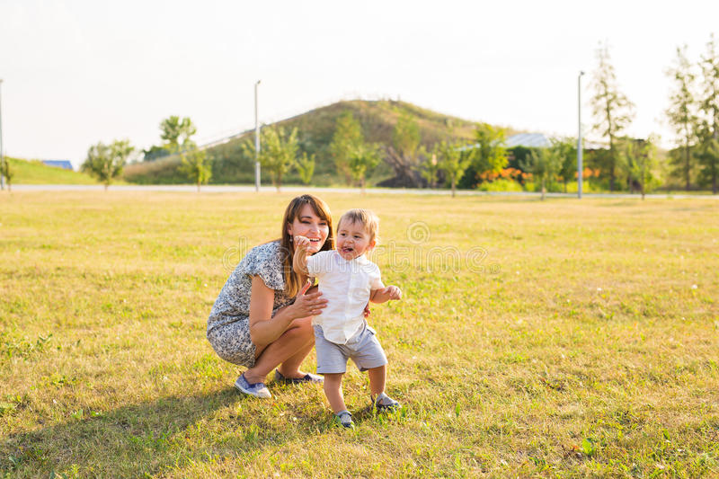 Happy young mother playing with her little baby son on sunshine warm autumn or summer day. Beautiful sunset light in a stock photography