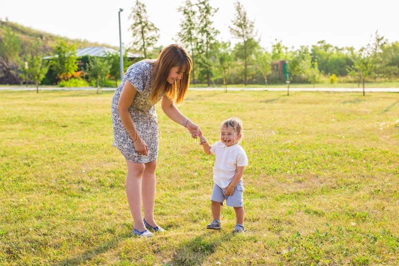 Happy young mother playing with her little baby son on sunshine warm autumn or summer day. Beautiful sunset light in a royalty free stock photos