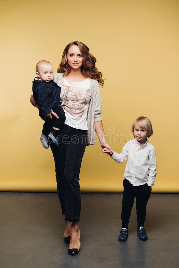 Happy young mother posing at camera together with her kids. royalty free stock images