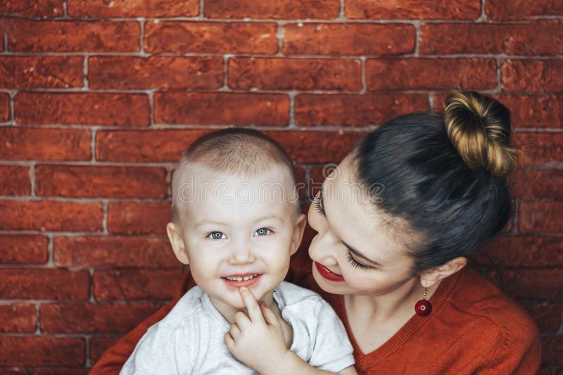 Happy and young mother sitting on brick background and holding her baby. Love and family concept. royalty free stock image