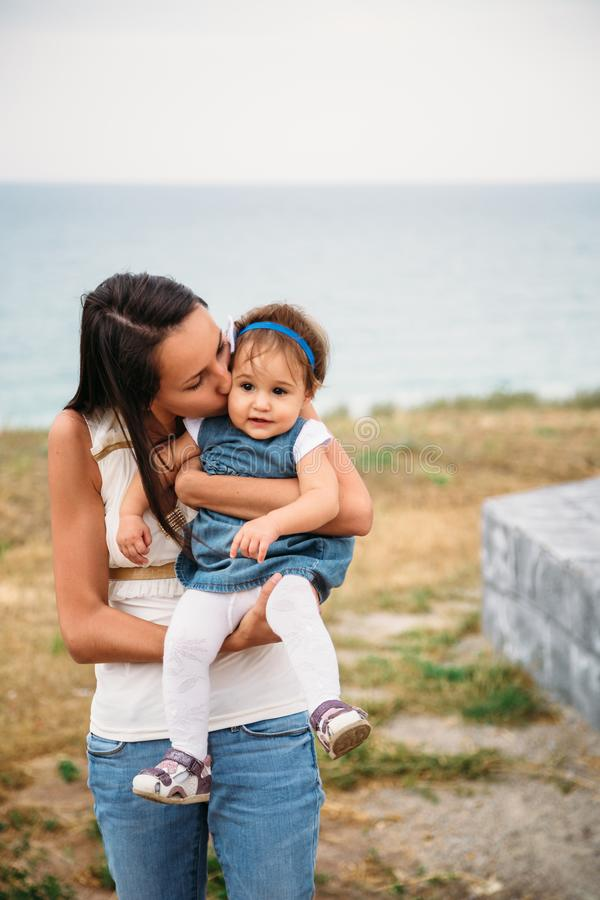 Happy young mother with a small daughter in hands hugging near to the lighthouse, outdoors background royalty free stock photography