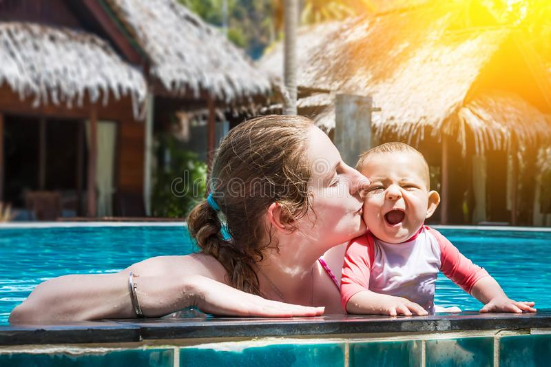 Happy young mother with a small infant baby in the pool outdoors. A woman kisses her joyful, opened his mouth and laughing child royalty free stock photography