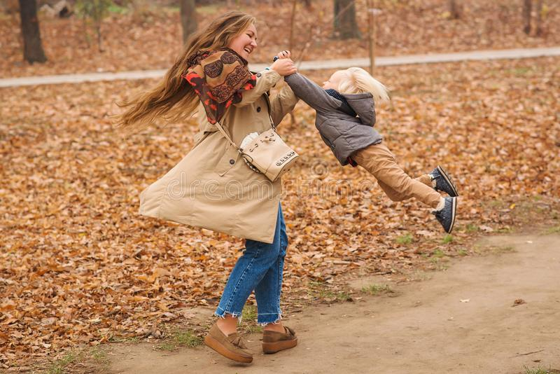 Happy young mother is spinning with her cute son in autumn park. Autumn, fashion, lifestyle. Happy family relationships. Stylish royalty free stock photo