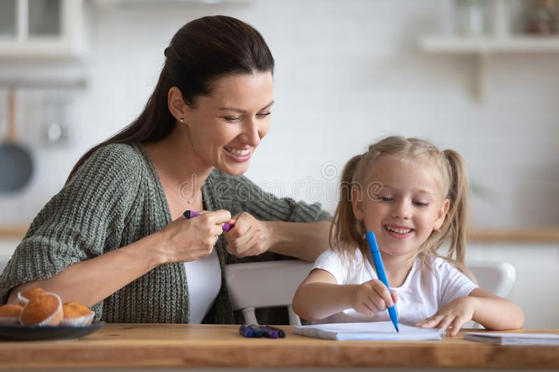 Happy young mother teaching drawing pictures little daughter. stock image