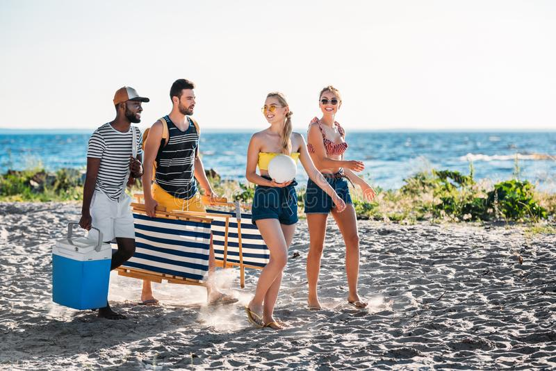 happy young multiethnic friends with beach chairs cooler and ball walking royalty free stock photos