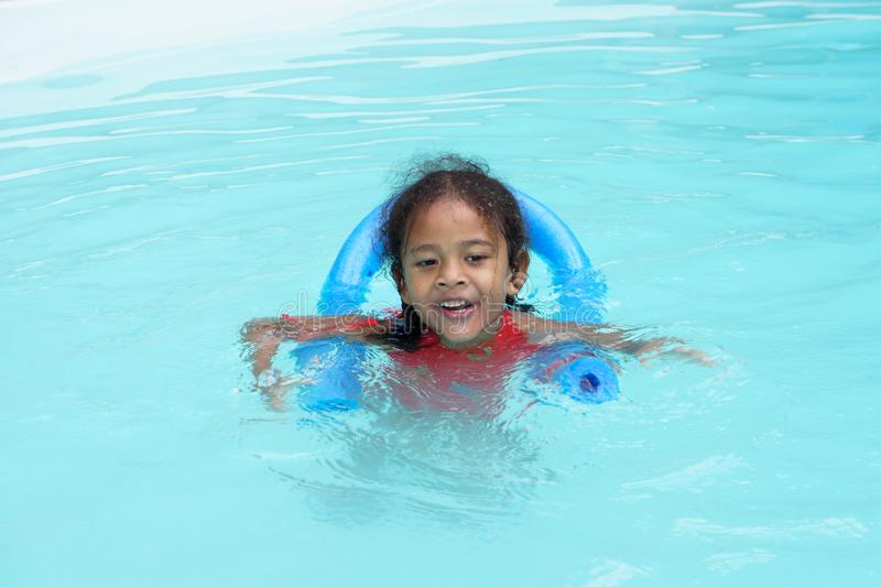 Happy young multiracial girl child learning to swim royalty free stock image