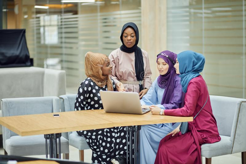 Muslim asian and african women in head scarfs and hijab using laptop in cafe royalty free stock photography