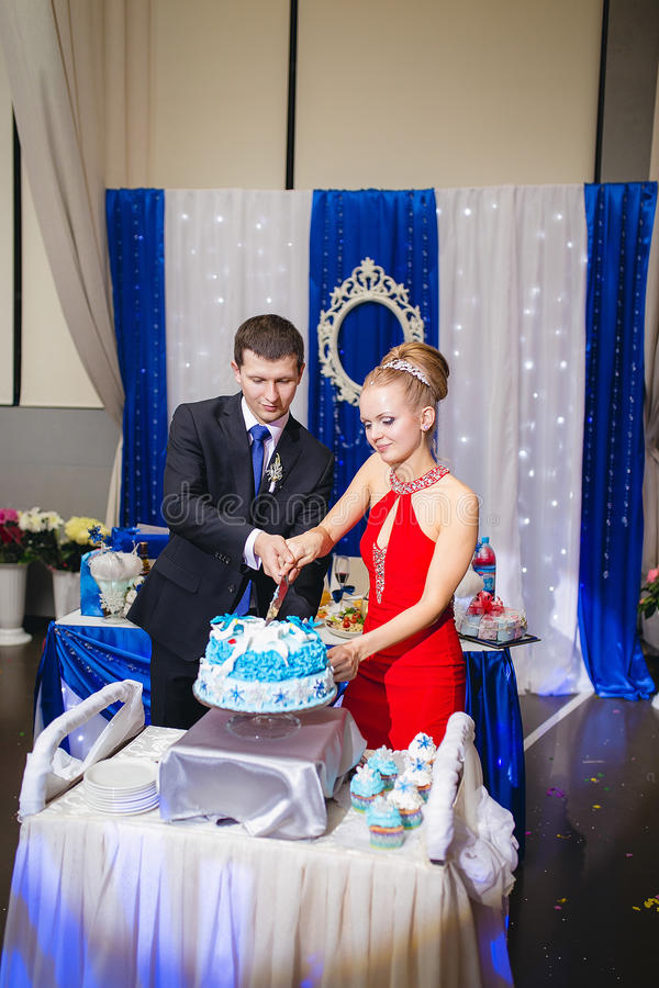 Happy young newlywed couple cutting wedding cake at banquet.  stock images