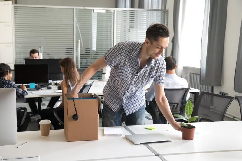 Happy young office worker, intern unpack belongings at workplace. Happy young man, intern unpack cardboard box with belongings at workplace, starting work in new stock images