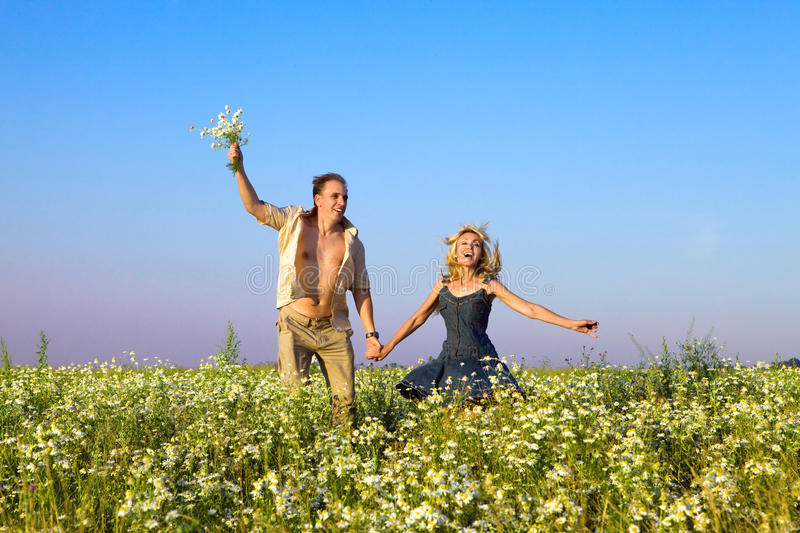 Download The Happy Young Pair In The Field Of Chamomiles Ju Stock Photo - Image of pair, girl: 16865644
