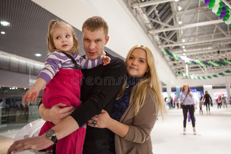 Happy young parents ice skating with their small daughter stock photography