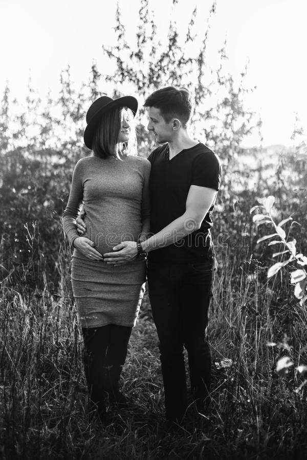 Happy young parents, mom and dad, hugging baby bump, walking and smiling, enjoying beautiful moment at sunset. Stylish pregnant. Couple holding hands on belly royalty free stock image