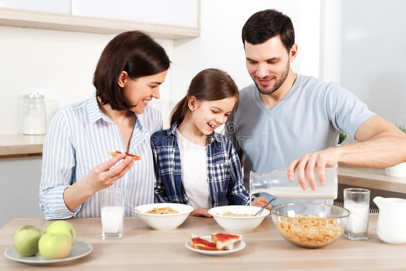 Happy young parents and their lovely daughter sit together at kitchen table, eat flakes, have healthy breakfast, enjoy royalty free stock image