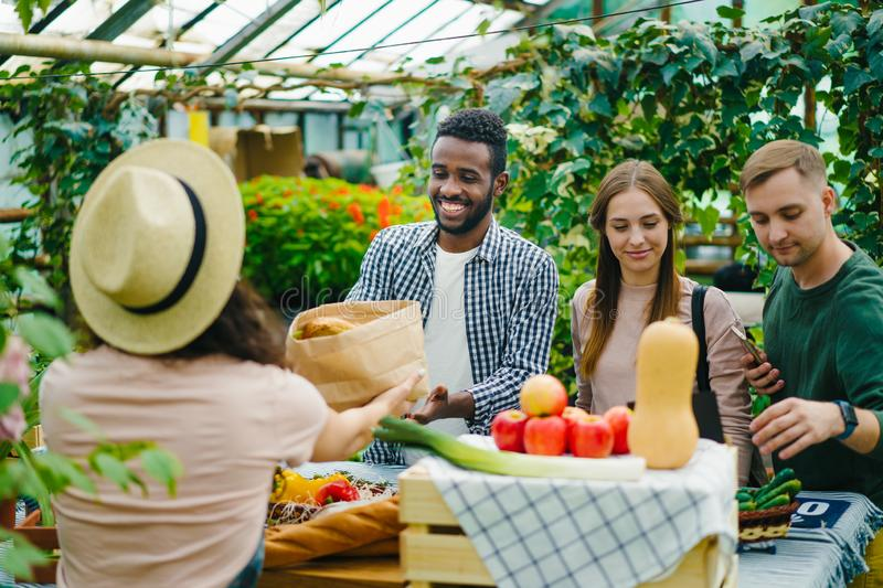 Happy young people buying organic food in market talking to female farmer stock photo