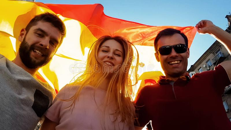 Happy young people celebrating victory of national Spanish team, sport tourism stock photo