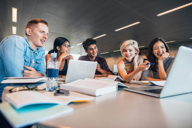 Happy young people doing group study in library stock photos