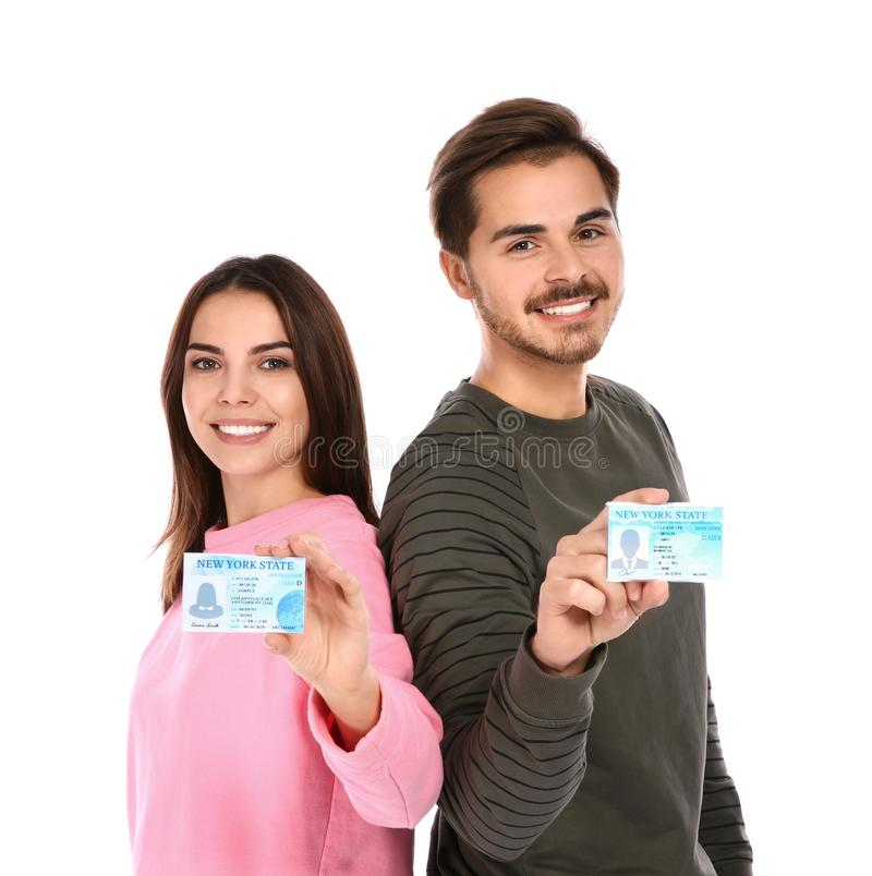 Happy young people with driving licenses. On white background royalty free stock photos