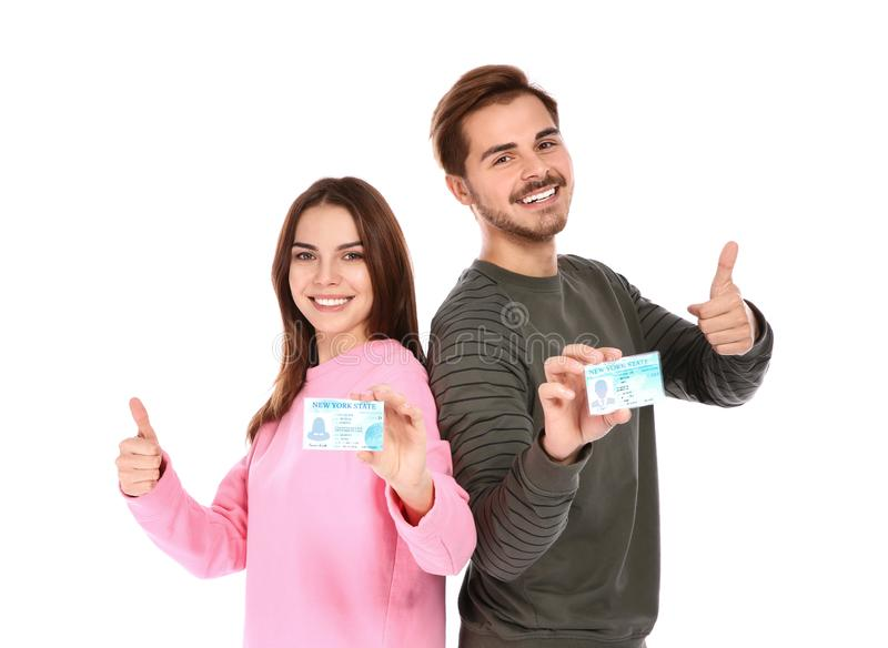 Happy young people with driving licenses. On white background stock photography