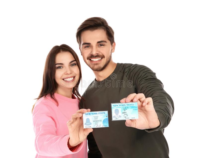 Happy young people with driving licenses. On white background royalty free stock image
