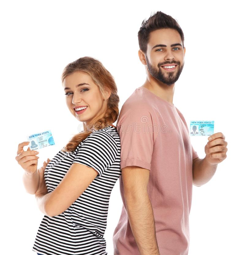 Happy young people with driving licenses on white. Background stock photos