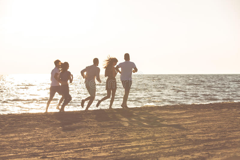 Happy young people group have fun white running and jumping on beach at sunset time stock photo