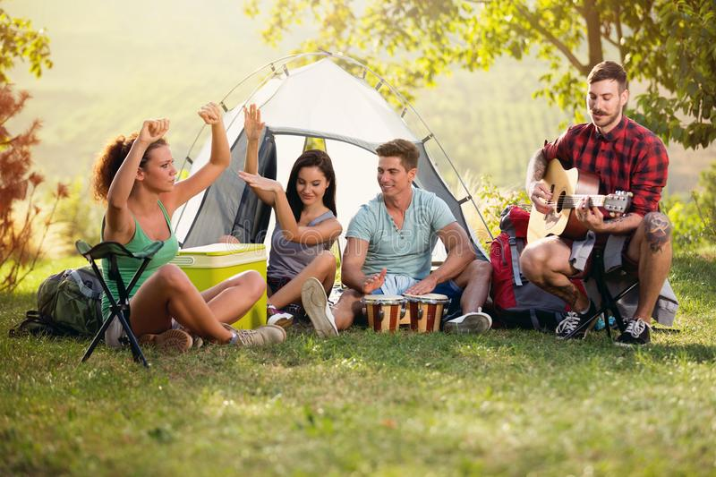 Happy young people having fun with music on camping trip royalty free stock image