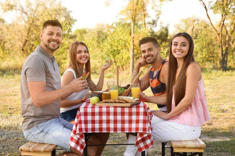 Happy young people having picnic at table royalty free stock photos