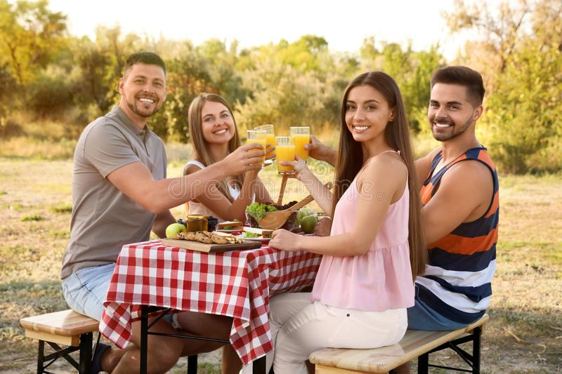 Happy young people having picnic at table stock image