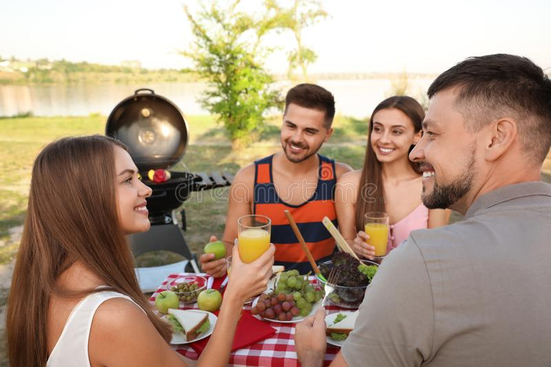 Happy young people having picnic at table stock images
