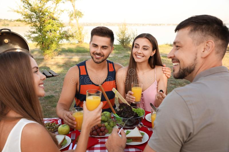 Happy young people having picnic at table royalty free stock image