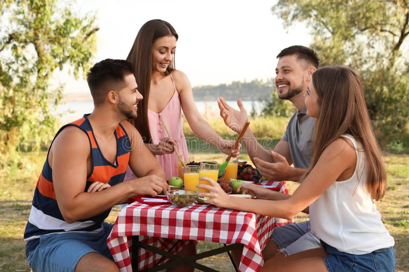 Happy young people having picnic at table stock photos