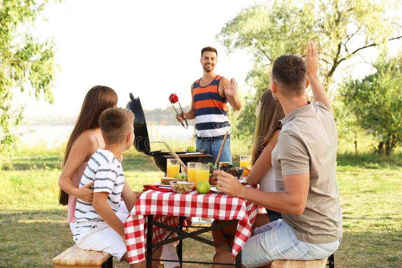 Happy young people and little boy having picnic at table stock photography