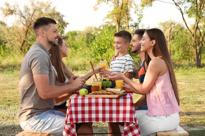 Happy young people and little boy having picnic at table stock photo