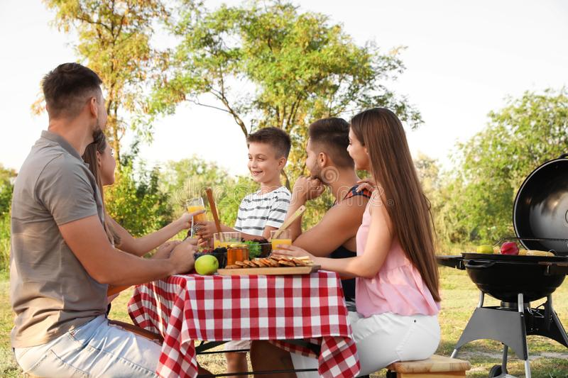 Happy young people and little boy having picnic at table royalty free stock image