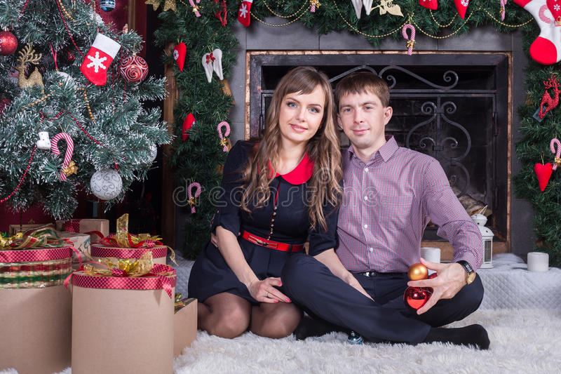Happy young people near the Christmas tree. stock images
